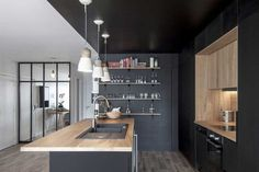 Black kitchen and wood: Example of real estate in an apartment - Dining Room