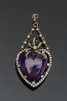 A late 19th/early 20th century amethyst and diamond heart pendant The heart-shaped amethyst in a diamond set claw mount, within a diamond surround, below a diamond set ribbon bow surmount, suspended on a later pearl set double chain suspension, from diamond set bale, total length 5.5cm.