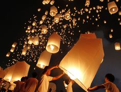 People launch floating paper lanterns into the sky