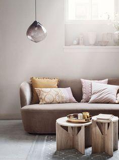 Tutto abbinato con cura: il lampadario in vetro leggermente scuro, il divano dalle linee morbide e la combinazione di tavolini in legno naturale.