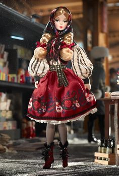"""From a gilded Imperial past to the chic modern present, fashion never takes a holiday in Russia. A revolution of brilliant reds and whimsical matryoshka dolls makes for scintillating style. Inspired by traditional, folkloric design, Mila™ Barbie® doll looks beguiling beneath her babushka."" (Bet she's from Ukraine!)"