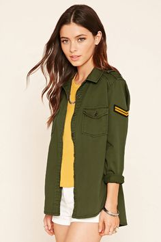 A lightweight woven utility jacket complete with a buttoned front, a chevron stripe patch on one arm, a basic collar, buttoned chest patch pockets, epaulets, long sleeves with buttoned cuffs, and a curved split hem.