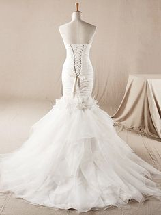 Sexy wedding dress is draped and pleated to create a stunning sculptural look. Strapless Taffeta bodice is accented with beaded flowers. Beaded floral embellishment is delicate on the mermaid gown. Back is corset closure. This dress is fully lined. #weddingdresses