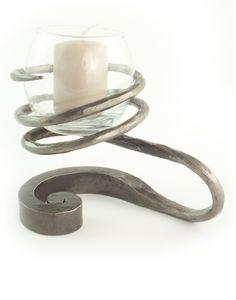 Photophore artisanal en fer forgé. En intérieur ou en extérieur, la lumière de la bougie illuminera agréablement vos soirées. A la base, ce bougeoir est une simple barre de fer, l'artisan ferronnier l'a travaillée avec une volute d'un côté, et a étiré le fer de l'autre pour créer cette spirale qui recueille le petit vase de verre. C'est une pièce unique !