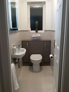 Small cloakroom. Grey lined wall and floor tiles edged with mosaic. Grey furniture surround with two storage cupboards. Hidden cistern. Small basin. Clean neat lines for a very small cloakroom.
