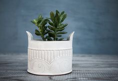Modern vase, made of white glazed ceramic with a mix pattern of stripes and spirals . This white ceramic winged vase is perfect for presenting your