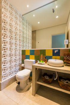 Os ladrilhos hidráulicos nas cores azul, amarelo, verde e salmão compõem este banheiro social, projetado pelas arquitetas Ananda Bello e Juliana Yamakawa do escritório BY Arq&Design. O tradicional box foi substituído por um cobogó branco.