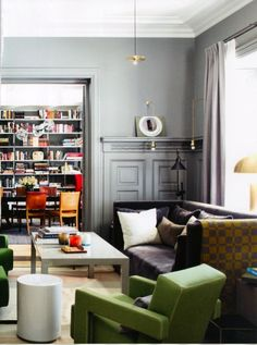Gray living room with library and green accent chair.