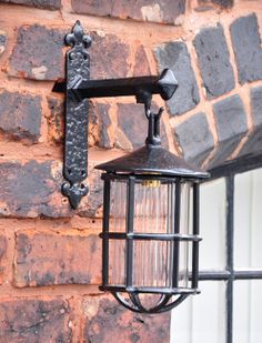 Kirkpatrick 403-W Hanging Lantern with Wall Bracket - This Kirkpatrick Lantern can be used internally or externally. The malleable iron bracket has a black antique finish which then holds the elegant lantern.  A great way to illuminate the way for visitors.