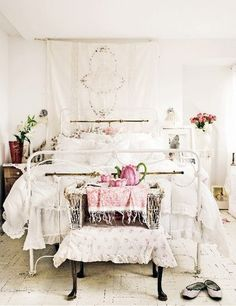 Beautiful white iron bed with fluffy white and pink comforter and dust ruffle.  shabby cottage and romantic