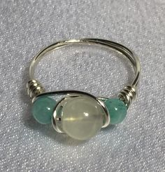 Handcrafted wire-wrapped Moonstone (June's birthstone) and Amazonite bead ring. Beads consist of one 7mm Moonstone and two 4mm dyed Amazonite. Wire is silver-plated anti-tarnish artistic wire. If you