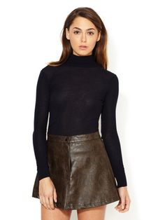 dark turtle neck sweater with leather mini and a side part