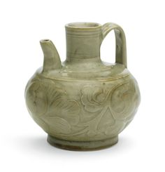 Lot 53| Sotheby's London 14 May 2014.  A CARVED 'YAOZHOU' CELADON 'PEONY' EWER SONG DYNASTY the compressed globular body supported on a spreading foot, the shoulder moulded with two raised fillets, surmounted by a cylindrical neck with triplet bow-string lines, set with a curved spout and loop handle, the exterior freely carved with a large peony bloom borne on bold leafy scrolls, covered overall in a translucent pale olive-green glaze firing to a russet-brown tone in areas 11cm., 4 3/8 in.