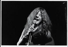 Cantor de rock bluesinfluenced americana Janis Joplin canta com paixão em um microfone com os olhos fechados enquanto ela executa em um palco escuro na ...