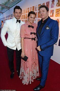 Three's company: Model David Gandy cosied up to Yasmin Le Bon and her husband Simon...