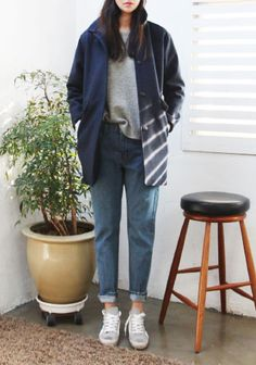 Denim blue wash mom/girlfriend jeans paired with an oversized grey marl sweatshirt, converse style trainers, and a tailored navy blazer.