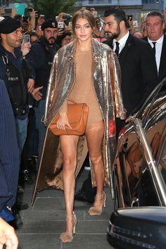 In a gold sequin coat, camel knit romper, fur sandals and camel handbag, all by Max Mara, at the Max Mara boutique in Milan