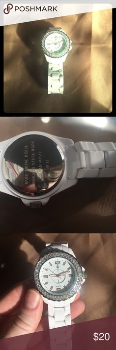 White watch Beautifully styled white watch. Never worn still has plastic protection on back of face. Watch is made of stainless steel. It has sparkles gems surrounding the face. Accessories Watches