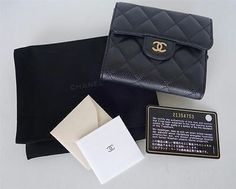 """This black quilted caviar leather compact wallet has a gold """"CC"""" logo on the front flap, and inside has six credit card slots, two open pockets behind the credit card slots, and a larger pocket for bills. The back of the wallet has a zippered coin compartment. Interior is made of brown leather. Comes with a Chanel pouch, authenticity card, and booklet. Hologram sticker marked with serial number: 21354753, which matches the authenticity card. Approximate Measurements: 4.66 inches across..."""