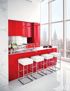 In a New York City residence by ODA-Architecture, the kitchen's red-lacquer cabinetry pops in the mostly-white space