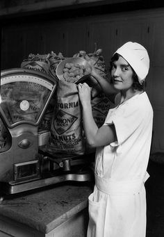 1929-Weighing Walnuts Nell McKibbin, a model rather than an actual worker, is demonstrating weighing and packing Diamond brand walnuts into a sack at the Walnut Growers Association packing house, located at 7th and Mill streets in Downtown Los Angeles.
