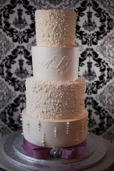 This buttercream wedding cake was encrusted with various size sugar pearls.  The monogram was piped and the brooch was made from gumpaste.  The ribbon is actual ribbon the bride was using in her reception.