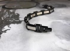 Un très beau bracelet en acier pour homme avec le mélange des couleurs noir et argent. Bracelets, Bangles, Birkenstock Milano, Sandals, Shoes, Jewelry, Black Colors, Steel, Beauty