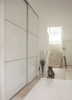ETEISEN VALKOISET LIUKUOVET  Espoolaisen omakotitalon eteisen liukuoviin on valittu puhdas valkoinen lasi ja kapea alumiinikehys. Laadukkaat mekanismit takaavat, että suuretkin ovet liukuvat kevyesti.