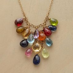 GEMSTONE TRIANGLE NECKLACE--Faceted briolettes in a rainbow of hues consisting of garnet, citrine, amethyst, ruby, peridot, andalucite, blue topaz, carnelian, kyanite, iolite, prehnite and pink tourmaline drip from a triangular chain link web. Handcrafted in USA of 14kt goldfill. By Thoi Vo. Approx. 15-1/2 to 18-1/2L