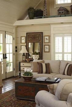 Neutrals. Love the shelf across the end of a high-ceiling room.