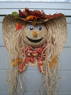 This scarecrow is made on an 18 inch straw hat. It is approximately 9 inches deep. On top of the hat are fall leaves, acorns, and berries. It has moveable eyes, a corn cob nose, and a brown felt mouth. The hair is raffia and has leaves in it that look like they have just fallen from the tree. There is a gold and orange bow under the neck.