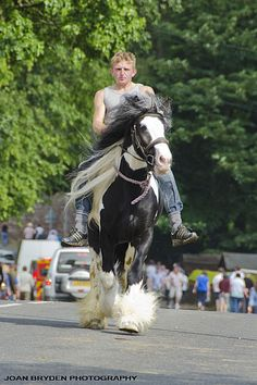 A young gypsy traveller rides bareback down the main street at the Appleby Horse Fair