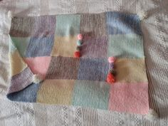 Stickad bebifilt med pom poms. Knitted baby blanket with pom poms