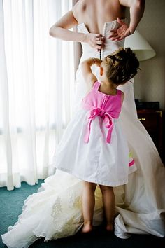Getting into the wedding gown is no easy feat — here, a flower girl does the honors of zipping up the bride.