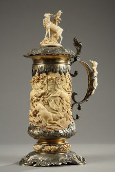 Silver and ivory jug finely sculptured with hunting scene composed of hunters, hinds, deers, dogs and billy goat atop. Scrolled handle decorated with a young woman wearing a floating drape. German work. c.1770