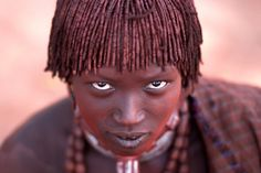 """The look"". The straordinary color upon the faces of the Hamer tribe in Jinka Ethiopia gived by the ground – Lo straordinario colore rosso che riflette la terra sui volti della tribu degli Hamer. Photo location:  Jinka, Ethiopia. (Photo and caption by Adam Ferlin/National Geographic Photo Contest)"