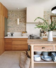 Rustic modern kitchen. Love the look of the stone wall there... if it would clean well. If I was enough of a minimalist, I could do without upper cabinets... or maybe just a few open shelves.
