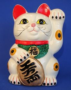 This lovely white lucky cat statue with left hand (paw) up is used to attract wealth and good luck to home or business. The cat's right hand (paw) is holding the symbol of money to represent wealth. It is made of porcelain and piggy bank too.
