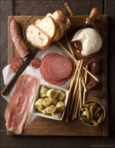 Antipasti: Prosciutto, salami, marinated peppers and artichokes, olive assortment, loaves of fresh bread, cheeses, nuts, etc..