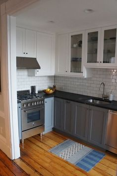 Dream kitchen style: gray lowers, white uppers with mix of shaker and glass doors, soapstone counters, and subway tile backsplash with gray grout. Only thing I'd change is the hardware! From Dan's Kitchen renovation on Apartment Therapy.