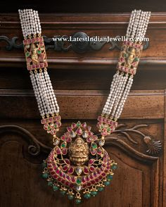 The multi string pearl rani haram attached to beautifully crafted Lakshmi devi pendant adorned with kundans and emerald drops from Kameswari jewelers Silver Jewellery Indian, Indian Jewellery Design, Golden Jewelry, Temple Jewellery, Pearl Jewelry, Latest Jewellery, Bridal Jewellery, Handmade Jewellery, Glass Jewelry