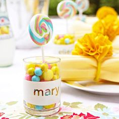 Candy Place Card  On a small glass cup, spell out a name with stickers. Tape around the top and bottom edge of the glass with painter's or masking tape. Using a pouncer brush, dab acrylic paint lightly over the letters to coat the area between the tape. Once dry, apply a second coat. Let dry, then peel off the letters and tape. Fill the cup with colorful candies and a lollipop for a sweet treat
