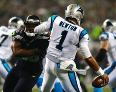 Carolina Panthers quarterback Cam Newton (1) is pressured by Seattle Seahawks defensive end Cliff Avril (56) during first quarter action at CenturyLink Field in Seattle, WA. on Saturday, January 10, 2015. The Seattle Seahawks hosted the Panthers in NFC Divisional Playoff action.
