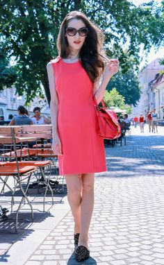 Fashion blogger Veronika Lipar of Brunette From Wall Street sharing how to wear peachy pink cocktail dress, black studded mules and hot pink bag this summer for a chic look