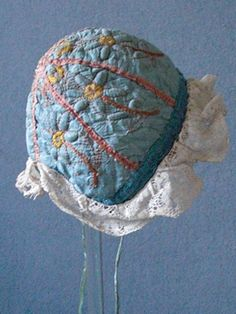 Baby bonnet, late 18th c, Pale blue silk segmented with pale pink silk picot edged ribbons, each segment embroidered with yellow outlined flower stem, their centers densely embroidered, a blue linen tape to the edge of the cap together with a hand made lace frill, narrow silk ties, lined with natural linen.