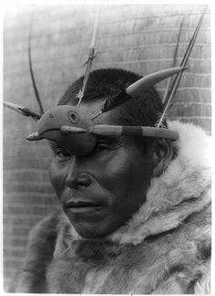 A Nunivak Cup'ig man with raven maskette. The raven (Cup'ig tulukarug) is Ellam Cua or Creator god in the Cup'ig mythology
