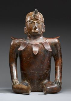 Seated Male Colima Mexico 100 BC- 300 AD This figure-as-vessel features a seated male of commanding presence. The dark red-slipped figure portrays a man with confident visage in a straightforward, commanding seated position. His hornlike protrusion...