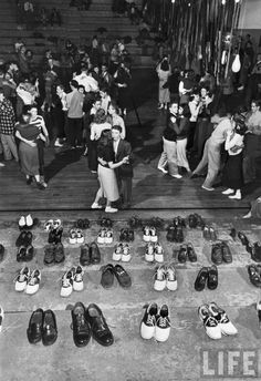 a sock hop, literally.  Shoeless teenage couples dancing in HS gym next to bleacher where rows of their shoes have been checked to avoid marring the facilitys hardwood floors during a Sock Hop, the latest craze to sweep the nations youth. Oklahoma, 1946 by Alfred Eisenstaedt (via LIFE)