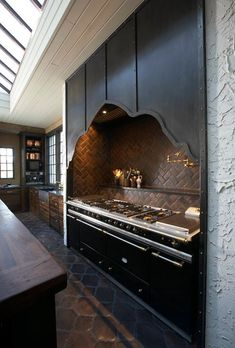 Tracery Interiors: Gothic iron kitchen design with butcher block kitchen island counter top, chevron ...