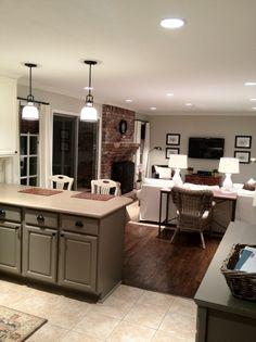 Kitchen tiled floor, dark flooring, brick fireplace, khaki paint.
